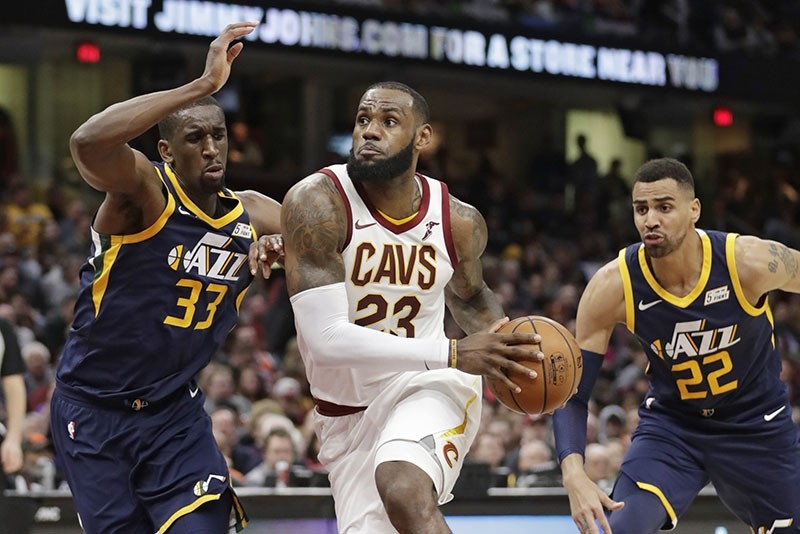 Cleveland Cavaliers' LeBron James, center, drives between Utah Jazz's Ekpe Udoh, left, and Thabo Sefolosha, from Switzerland, in the second half of an NBA basketball game, Saturday, Dec. 16, 2017, in Cleveland. (AP Photo)