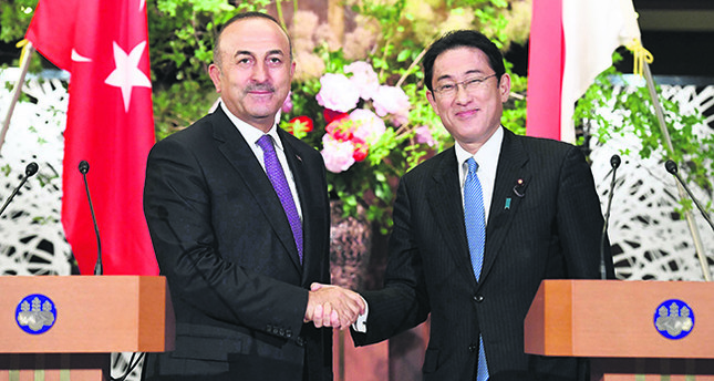 Foreign Minister Mevlüt Çavuşoğlu (L) shakes hands with his Japanese counterpart Fumio Kishida (R) during their joint remarks announcement at the foreign ministry's Iikura guesthouse in Tokyo on June 21.