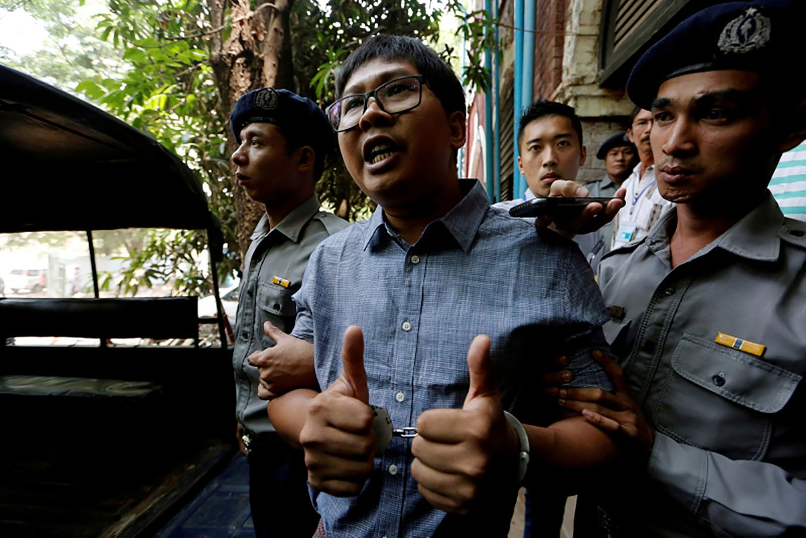 Detained Reuters journalist Wa Lone is escorted by police after a court hearing in Yangon, Myanmar April 4, 2018.