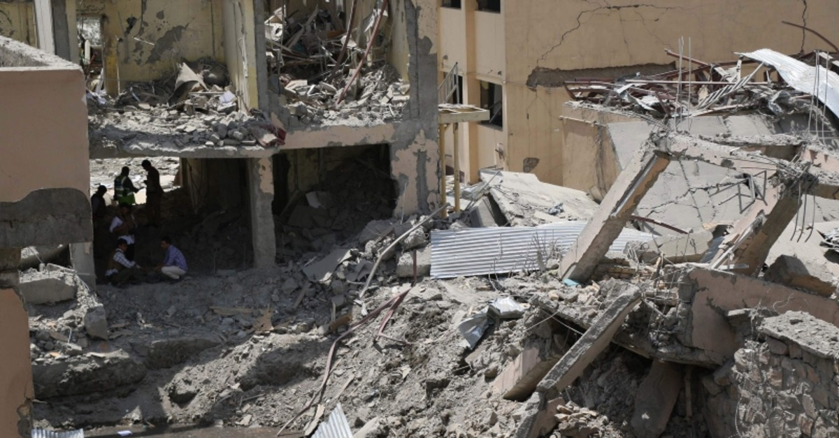Afghan security forces investigate the site where a Taliban car bomb detonated at the entrance of a police station in Kabul on Aug. 7, 2019.