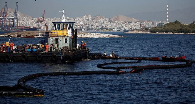 Workers take part in clean up and pollution containment operations at the area where a small oil tanker sank on September 10 off the shores of Salamina island, Greece, September 20, 2017. (Reuters Photo)