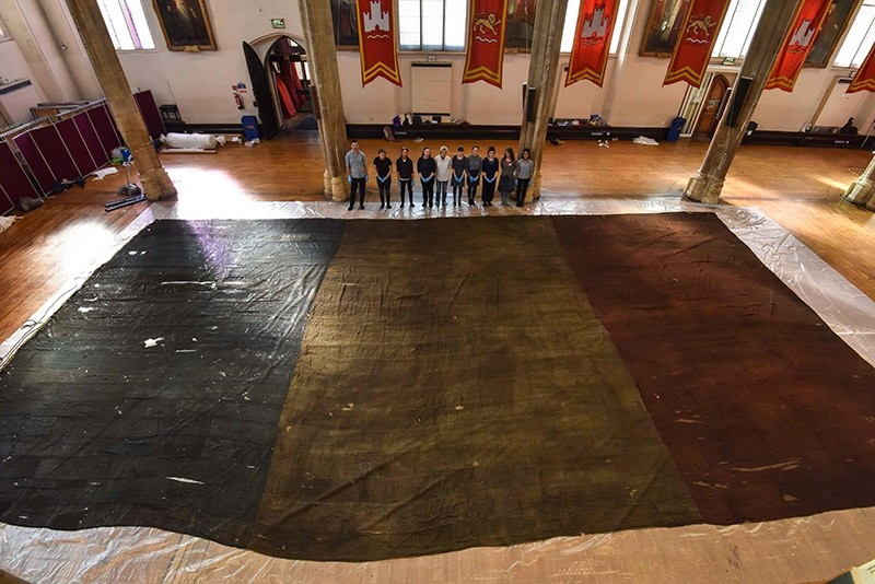 A handout picture released on February 15, 2017 by Norfolk museums service shows curators posing by a giant Tricolour flag at St Andrewu2019s Hall in Norwich in October 2016. (AFP)
