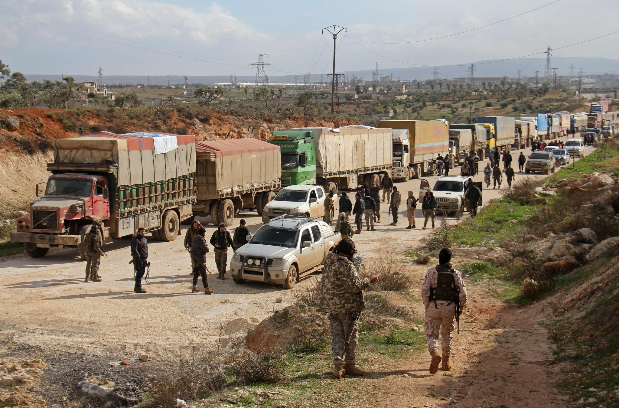Opposition fighters and aid workers stand near a convoy of vehicles carrying United Nations food and medical aid on the outskirts of Kafraya. (AFP Photo)