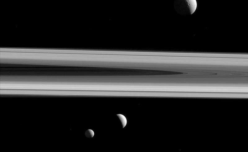 This Dec. 3, 2015 image made available by NASA shows three of Saturn's moons - Tethys, above, Enceladus, second left, and Mimas, seen from the Cassini spacecraft.