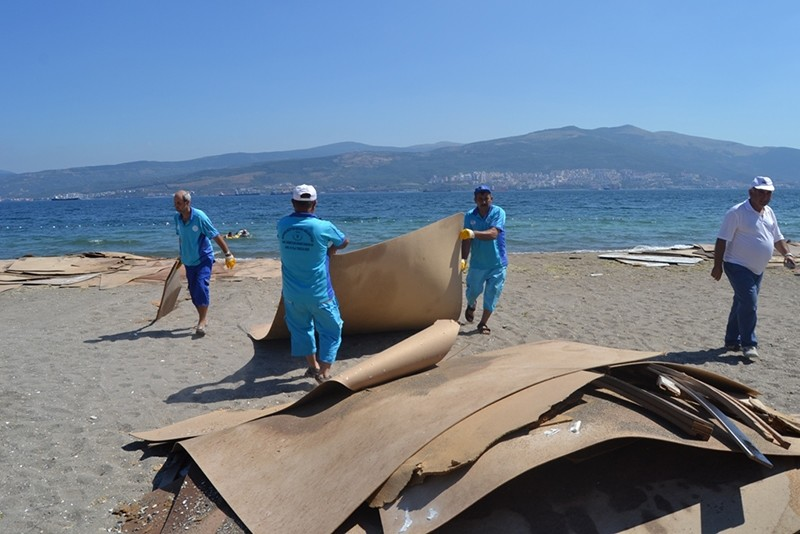 Workers cleaning up the seashore after Moldova-flagged ship spilled slit boards in Turkey's Gemlik district, Bursa province (DHA Photo)