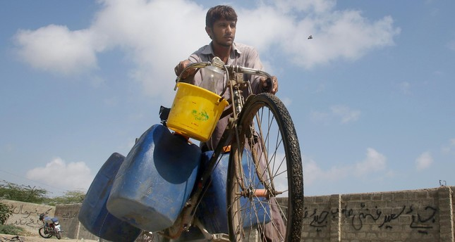A man who delivers drinking water to homes pushes his bicycle to collect water from community taps, Karachi, Pakistan.