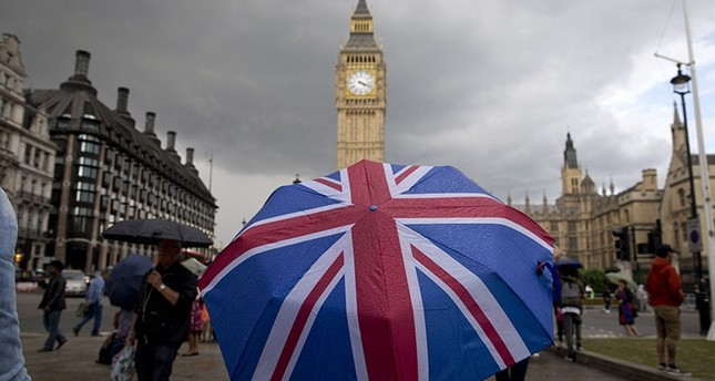 Pedestrian shelters from rain beneath Union flag themed umbrella as they walk near Big Ben clock face and Elizabeth Tower at Houses of Parliament in London on June 25, 2016 (AFP)