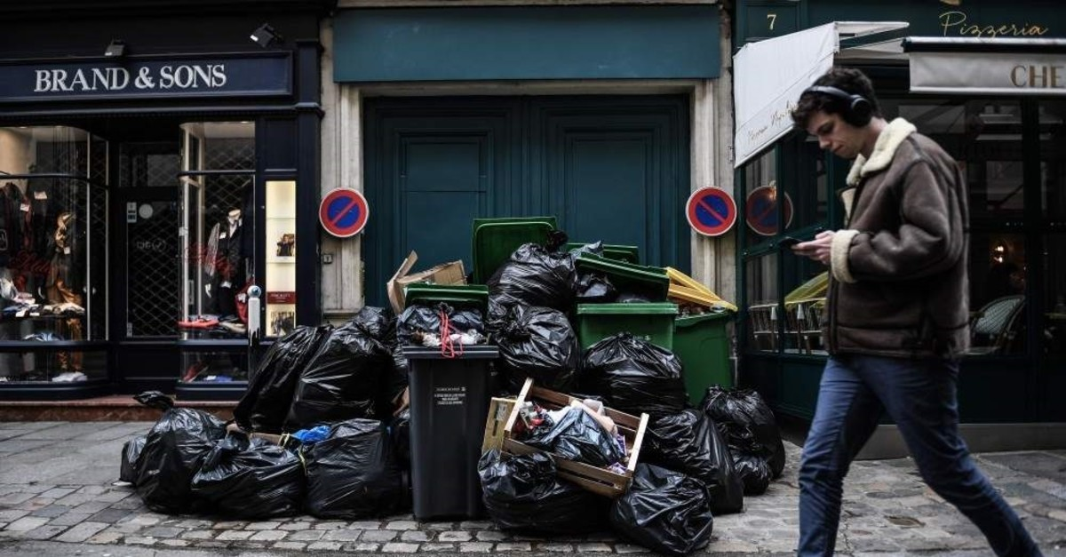 A man walks past garbage piled in a street of Paris following the blockade of incinerators around the French capital, Feb. 3, 2020. (AFP Photo)