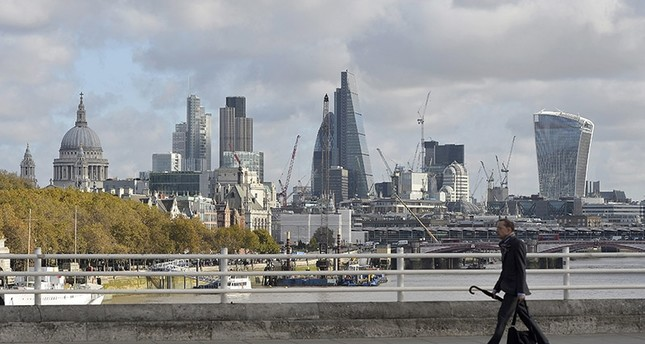 A man crosses Waterloo Bridge with the backdrop of the city of London and the financial district in London, Britain, 07 November 2016. (EPA Photo)