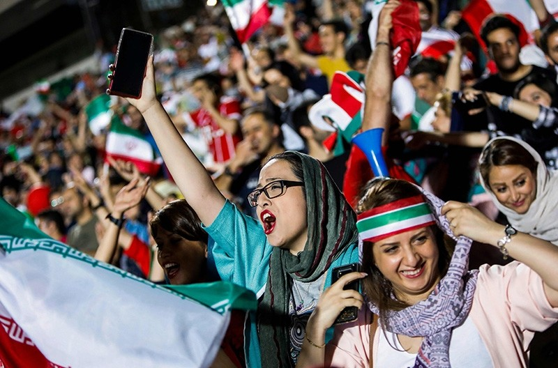 Iranian football supporters wave their national flags as they cheer for their national team during a screening of the Russia 2018 World Cup Group B football match between Iran and Spain in Azadi stadium in Tehran on June 20, 2018. (AFP Photo)