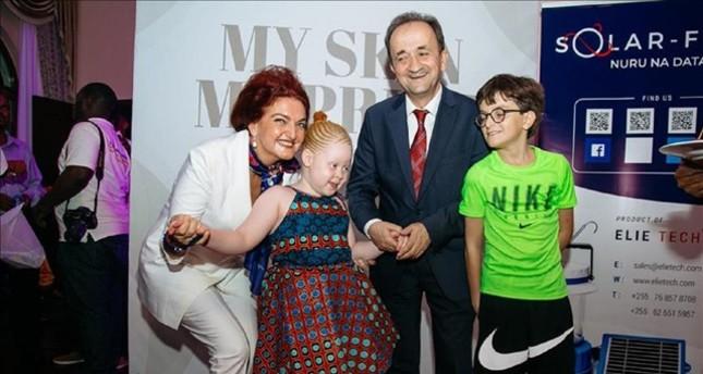 Yeşim Davutoğlu and Ali Davutoğlu with an albino girl.