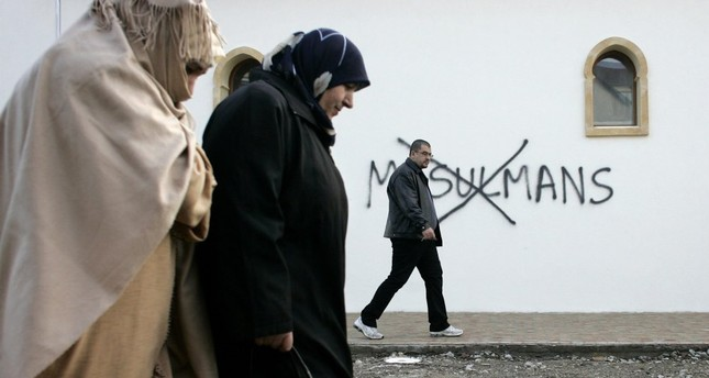 Muslim residents walk past anti-Islam graffities painted on the walls of a mosque in the town of Saint-Etienne, central France,  Feb. 8, 2010.
