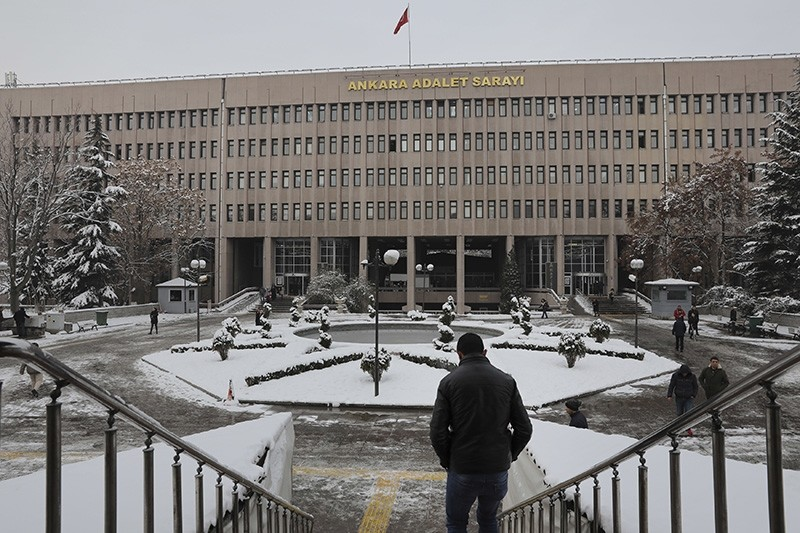 A man walks towards a court in Ankara, Turkey, on Tuesday, Jan. 8, 2019, where a trial has opened against 28 people accused of involvement in the 2016 killing of Russia's ambassador to Turkey. (AP Photo/Ali Unal)