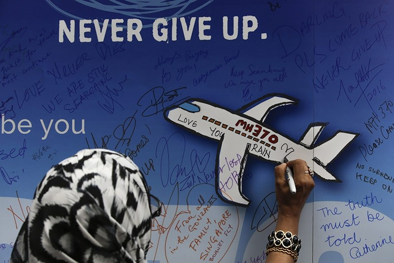 A file picture dated 06 March 2016 shows a woman writing messages for the passengers of missing Malaysia Airlines flight MH370 on a banner during a remembrance ceremony in Kuala Lumpur, Mayaysia. (EPA Photo)