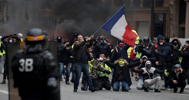 A protester waves a French flag during clashes with police at a demonstration by the yellow vests movement in Paris, Dec. 8.