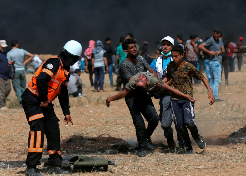 Palestinian protesters and paramedics carry an injured demonstrator away from the scene of clashes with Israeli forces, along the border with Israel, east of Khan Yunis in the southern Gaza Strip on June 8, 2018. (AFP PHOTO)