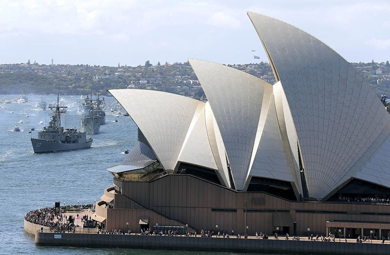 In this Oct. 4, 2013, file photo, the Opera House is seen as Australian warships from front, HMAS Sydney, Darwin and Perth enter the harbour in Sydney, Australia, during the International Fleet review. (AP Photo)