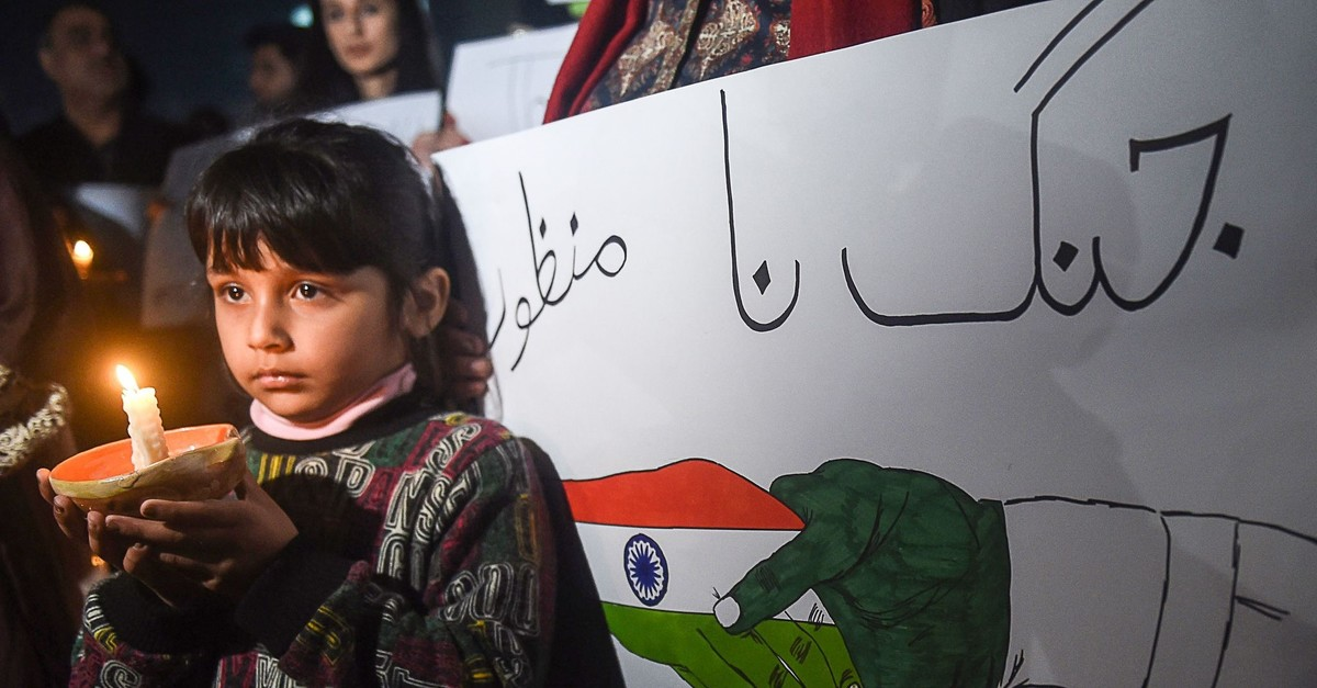 A Pakistani girl holds a lighted candle during a vigil for peace in Lahore; tensions have soared between India and Pakistan since a suicide bombing in Kashmir, March 3, 2019.