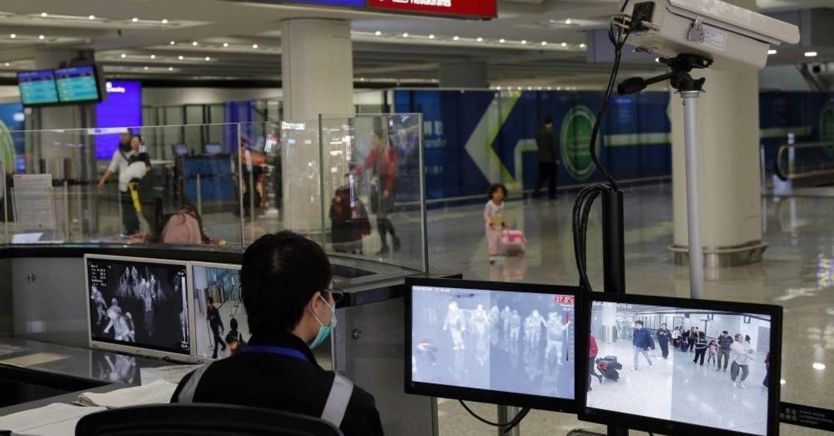 A health surveillance officer monitors passengers arriving at the Hong Kong International airport, Hong Kong, Jan. 4, 2020. (AP Photo)