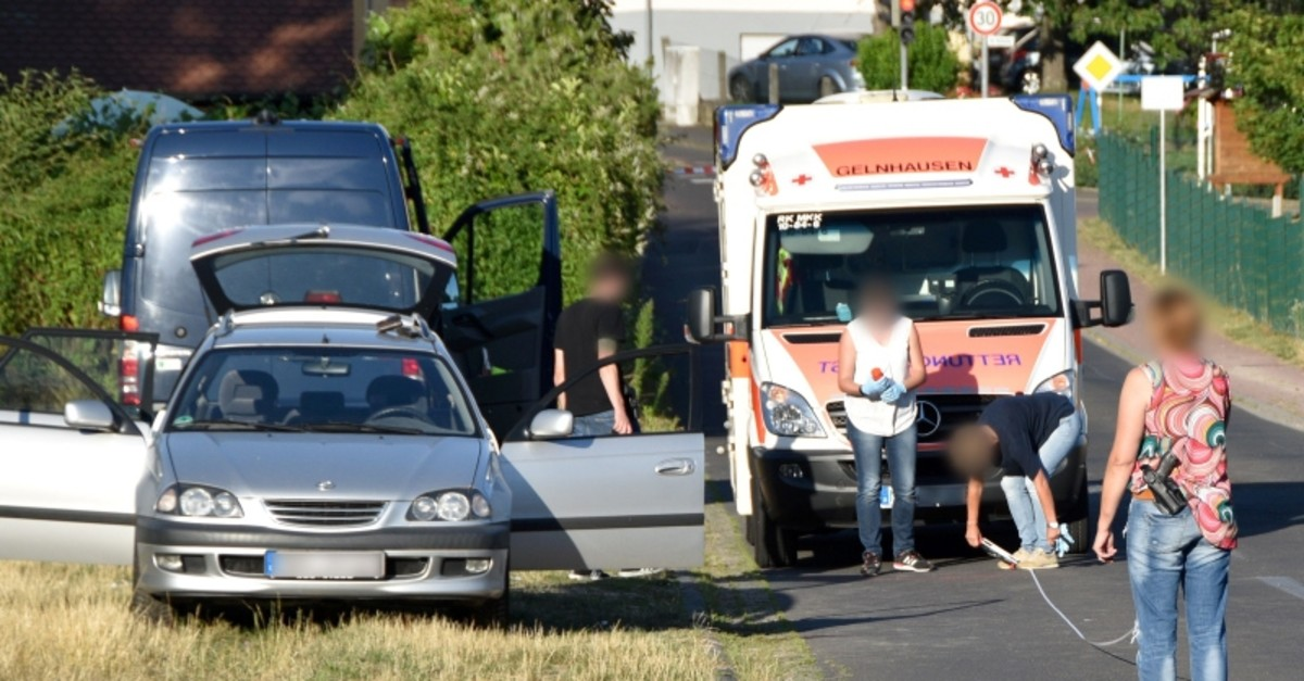 Picture taken on July 22, 2019 shows policemen securing evidences close to an ambulance car and a passenger car in Biebergemuend near Bad Orb, western Germany (AFP Photo)