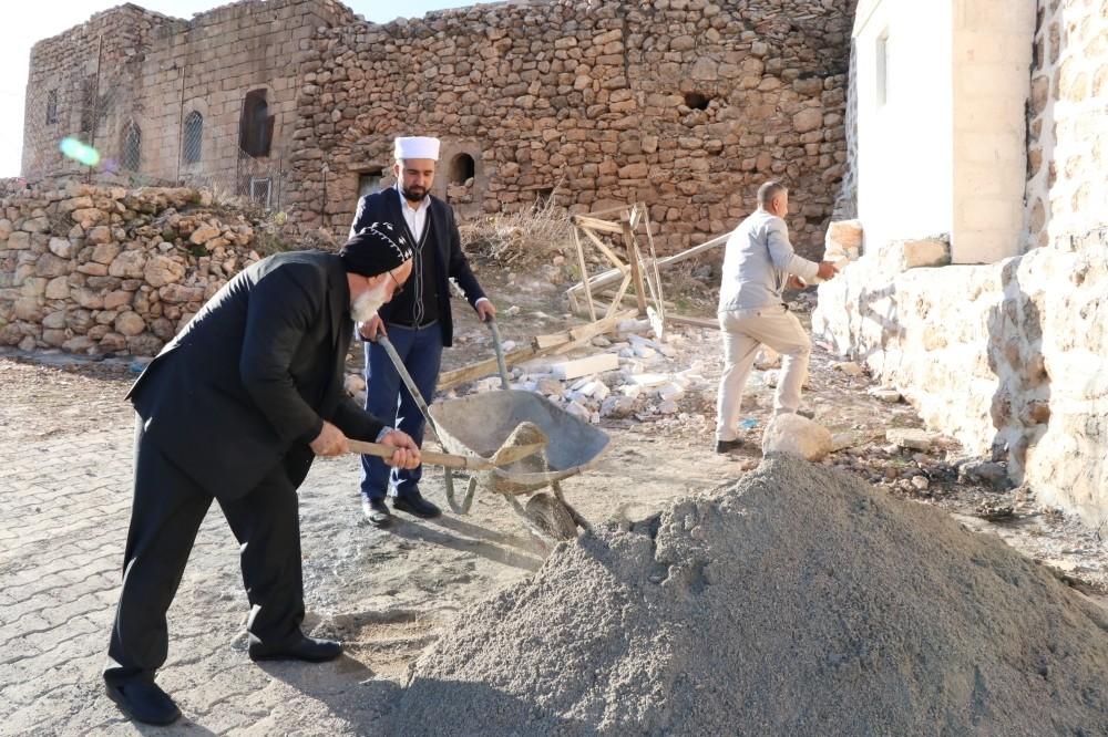 Rev. Savcu0131 shovels sand into a cart carried by imam Kardau015f.