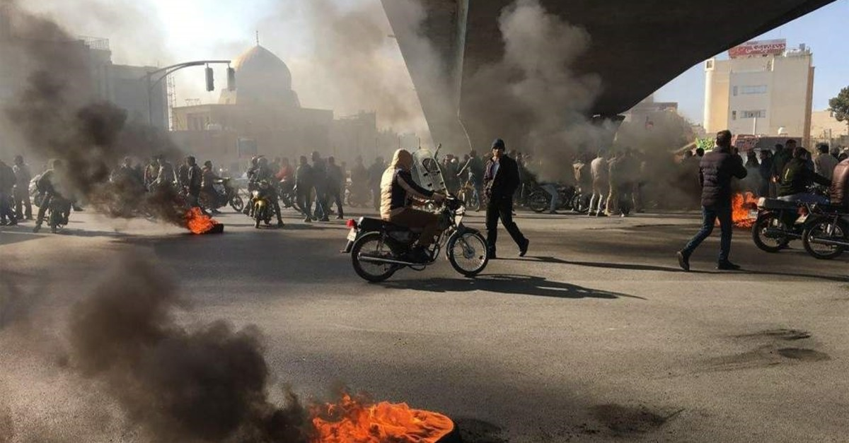 Iranian protesters rally amid burning tires during a demonstration, Isfahan, Nov. 16, 2019. (AFP Photo)