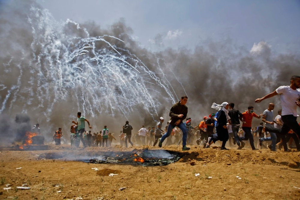 Palestinians run for cover from tear gas during clashes with Israeli security forces near the border between Israel and the Gaza Strip, May 14, 2018.