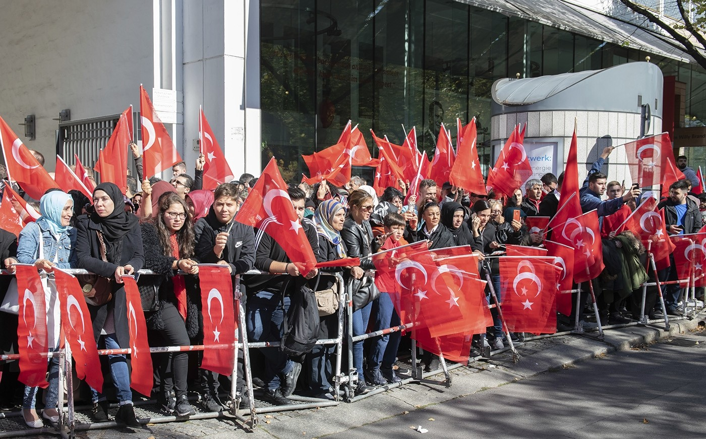 Fans of Turkish President Recep Tayyip Erdoğan hold Turkish flags while waiting for his arrival to a hotel in Berlin Thursday, Sept. 27, 2018. (AP Photo)