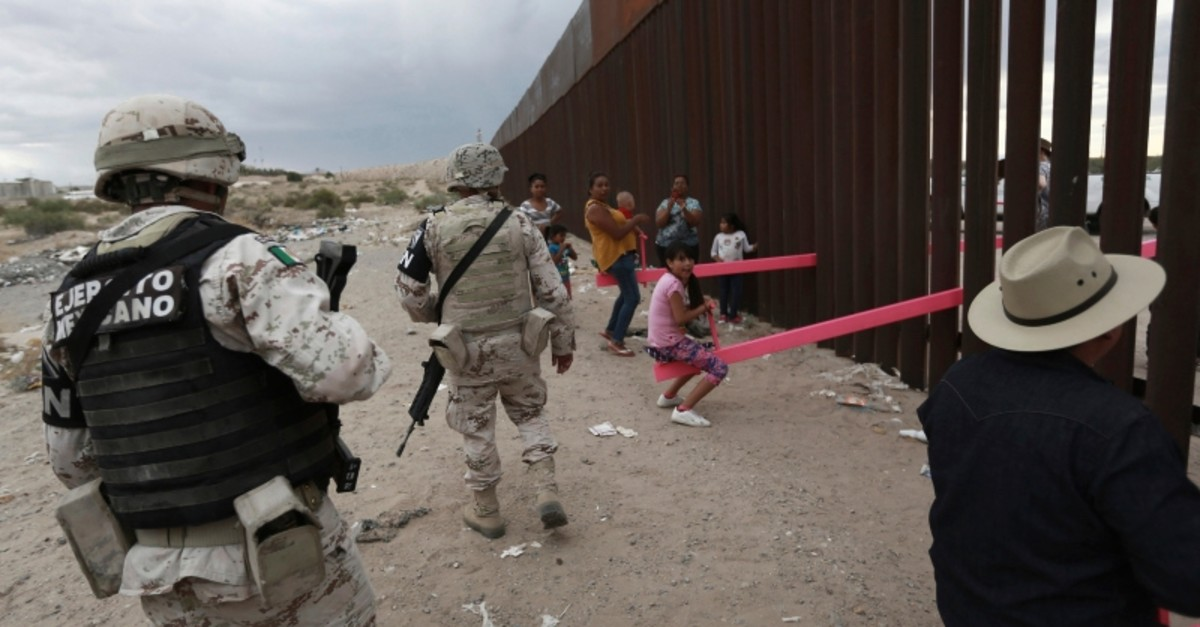 Members of the Mexican military police wearing the insignia of the new National Guard check children and people as they play seesaw installed between the border fence that divides Mexico from the United States in Ciudad de Juarez, Mexico (AP Photo)