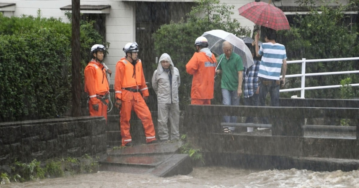 Members of the fire department monitor the water level of the Wada River in heavy rain Wednesday, July 3, 2019, in Kagoshima City, southwest Japan. (Kyodo News via AP)