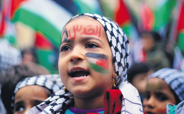 A girl with a Palestinian flag and Jerusalem is for us painted on her face in Arabic, chants slogans during a sit-in in the Bourj al-Barajneh Palestinian refugee camp in Beirut, Lebanon Dec. 6.