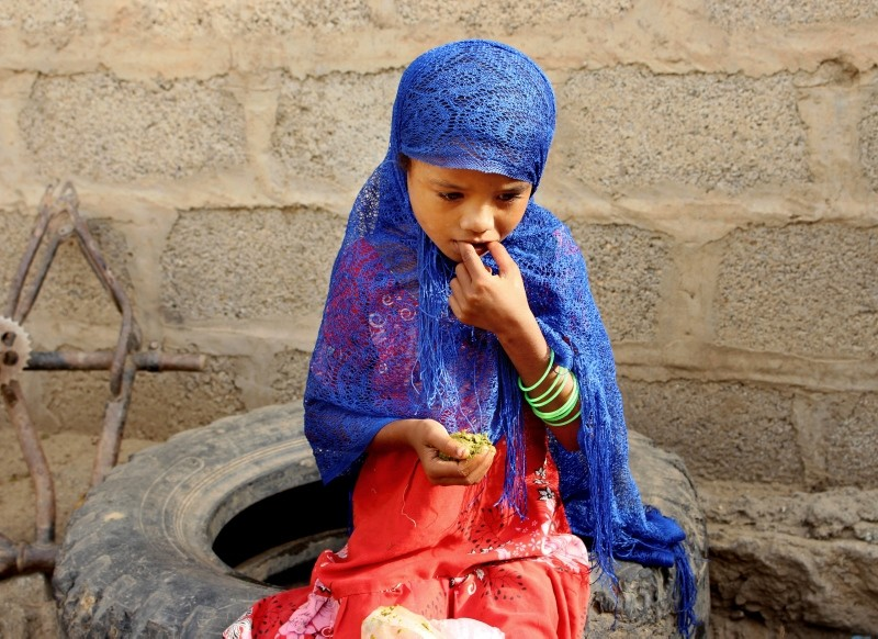 In this Aug. 25, 2018 photo, a girl eats boiled leaves from a local vine to stave off starvation, in the extremely impoverished district of Aslam, Hajjah, Yemen. (AP Photo)