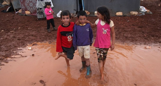 Internally displaced Syrian children pose for a photograph in a flooded refugee camp in the Idlib countryside, northwestern Syria, Oct. 25.