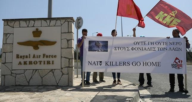 محتجون أمام القاعدة العسكرية البريطانية (رويترز)