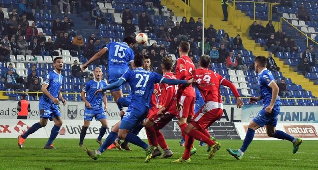 Footballers of Sarajevo's Zeljeznicar FC (blue jerseys) take part in a local match against Mladost FC (red jerseys).