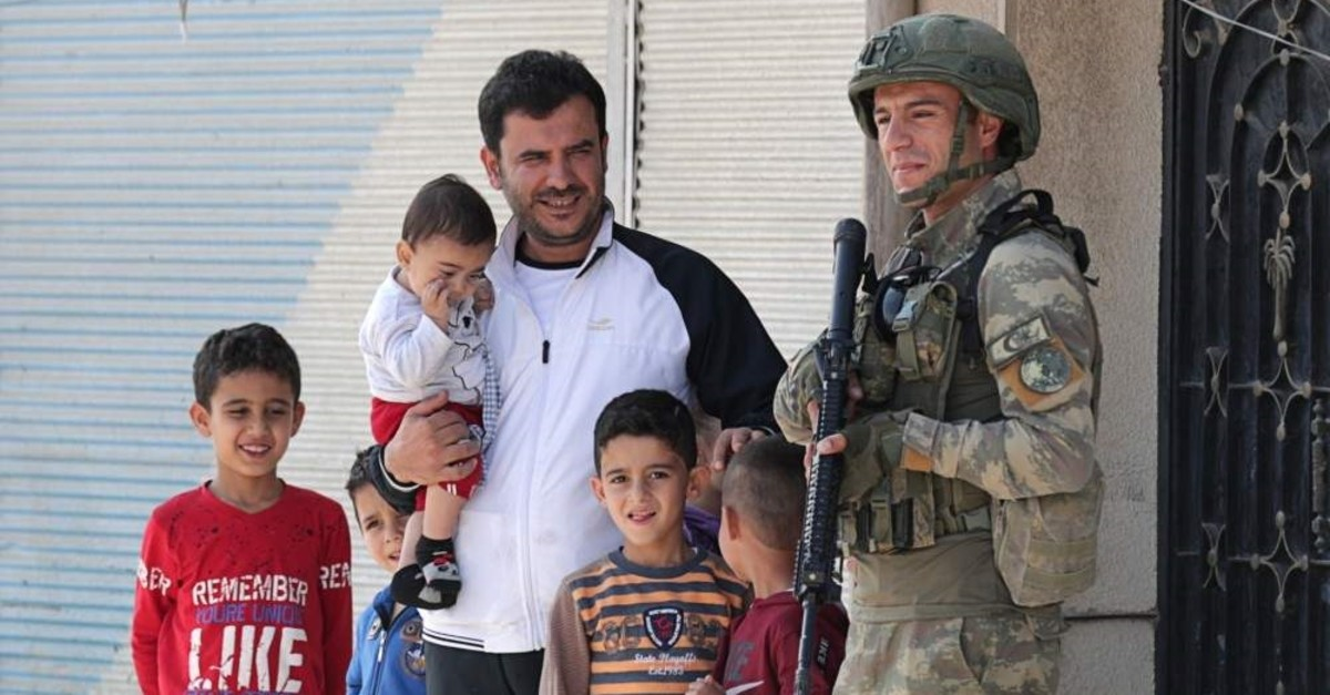 A man with children stands next to a Turkish soldier in the town of Tal Abyad after the area was cleared of terrorist elements, Oct. 23, 2019. (REUTERS)