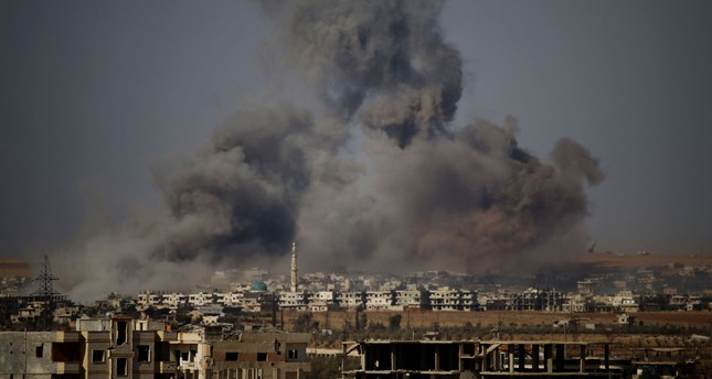 Smoke rises above an opposition-held town east of the city of Daraa during airstrikes by Syrian regime forces, June 30.
