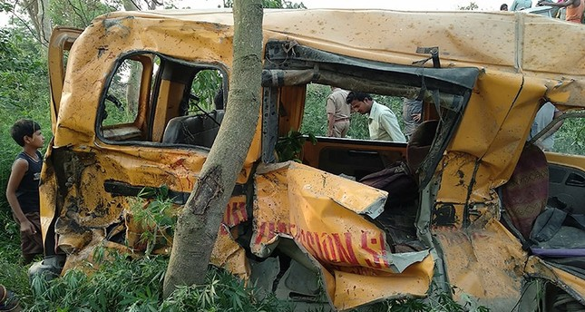 Onlookers gather around the mangled remains of a school bus after it was hit by a train in Kushinagar district in India's Uttar Pradesh state on April 26, 2018. (AFP Photo)