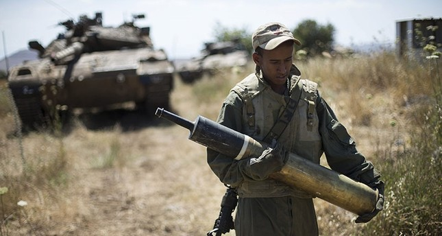 An Israeli soldier carries a tank shell near Alonei Habashan on the Israeli occupied Golan Heights, close to the ceasefire line between Israel and Syria June 22, 2014. (Reuters Photo)