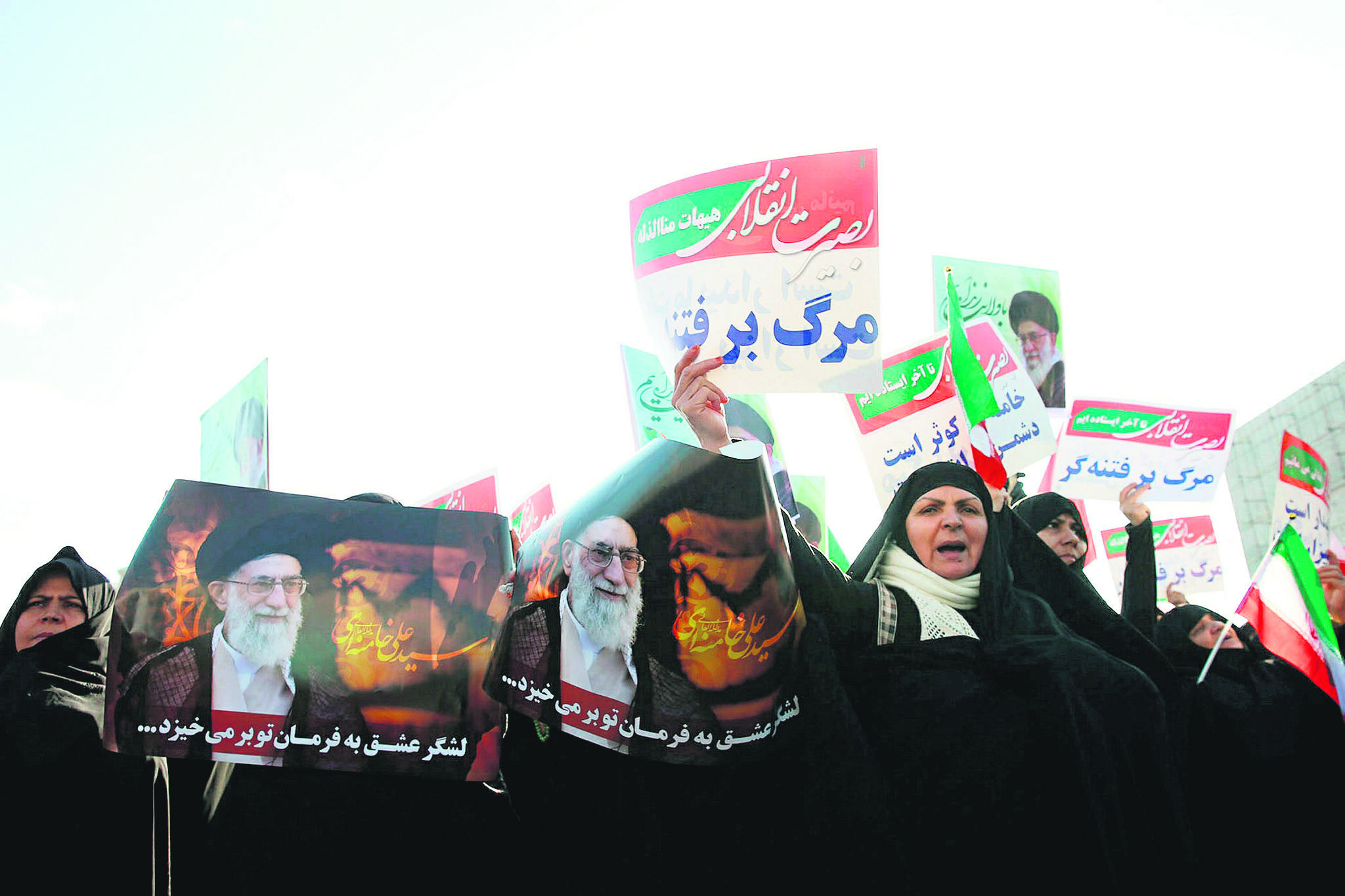 Iranian pro-government supporters hold posters of Supreme Leader Ayatollah Ali Khamenei during a rally in support of the regime after authorities declared the end of deadly unrest, Mashhad, Jan. 4.