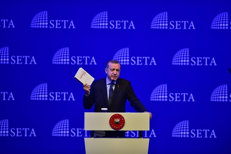 President Erdou011fan holds a SETA publication on the proposed presidential system, which will be voted in a referendum on April 16. (Sabah Photo)