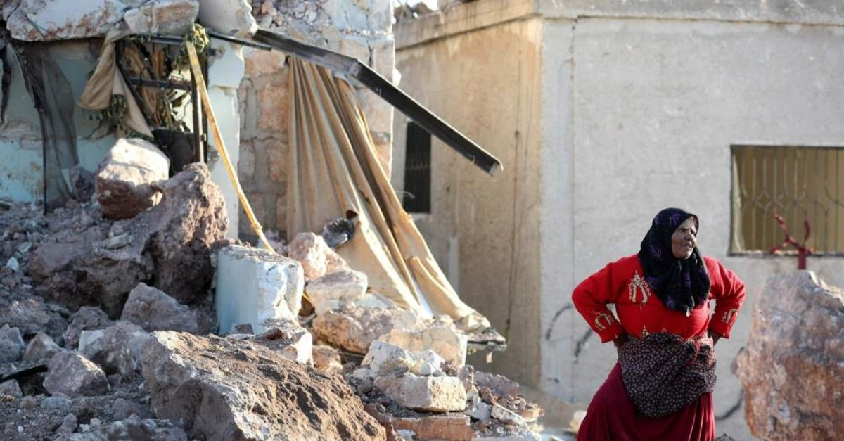 A woman stands amid the rubble of a building that was reportedly destroyed during airstrikes by the Syrian regime's ally Russia, Idlib, May 20, 2019.