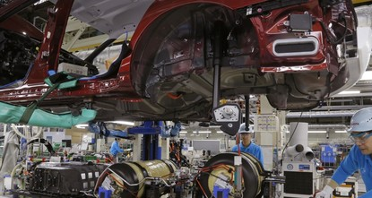 pAt a car factory in this city named after Toyota, the usual robots with their swinging arms are missing. Instead, workers intently fit parts into place by hand with craftsmanship-like care. The...