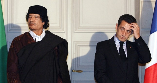In this file photograph taken on Dec.10, 2007, then French President Nicolas Sarkozy (R) and Libyan leader Moamer Kadhafi pose during the signature of 10 billion euros of trade contracts between the two countries in Paris. (AFP Photo)