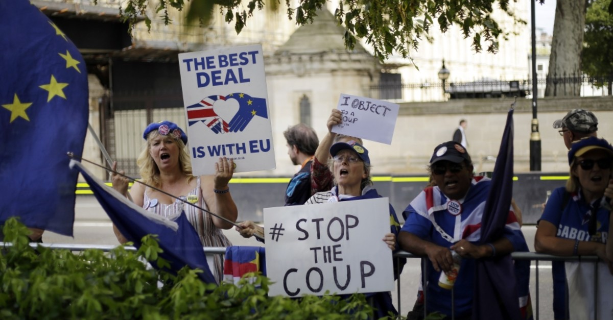 Anti-Brexit protesters wave flags and hold signs near the Houses of Parliament, London, Aug. 28, 2019.