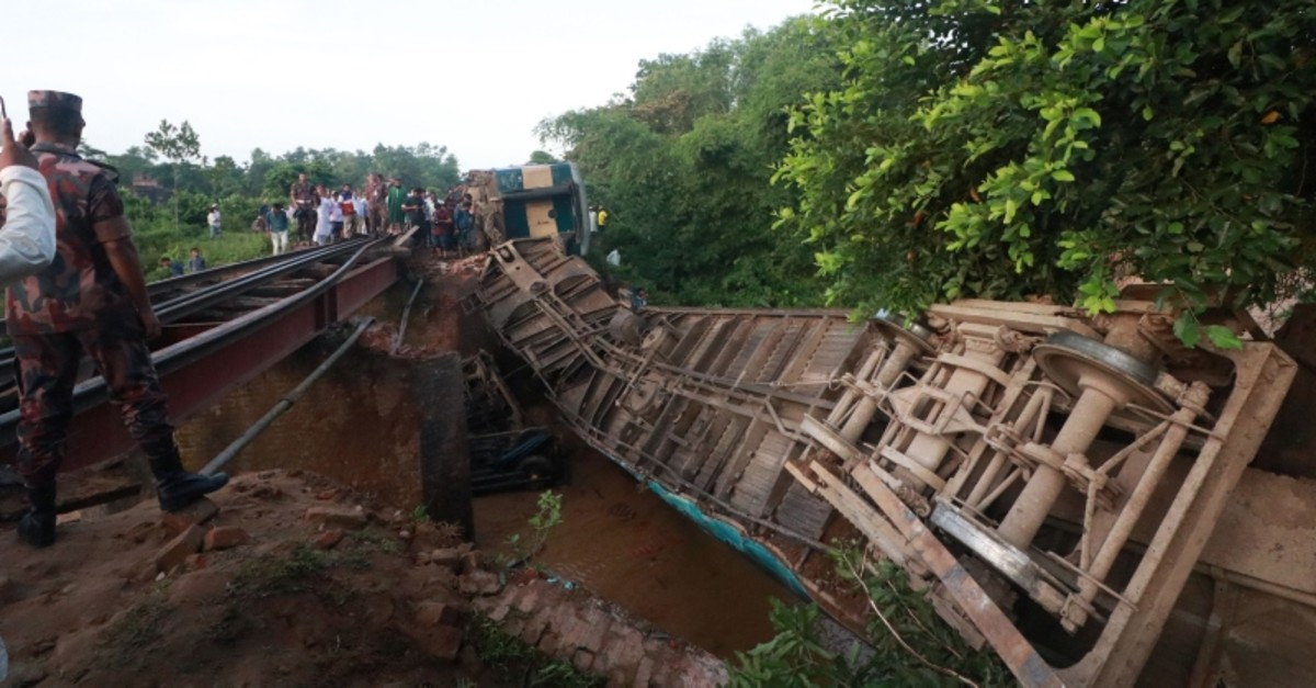Bangladeshi onlookers gather around a derailed train after a bridge collapse in Kulaura on June 24, 2019. (Photo by STR / AFP)