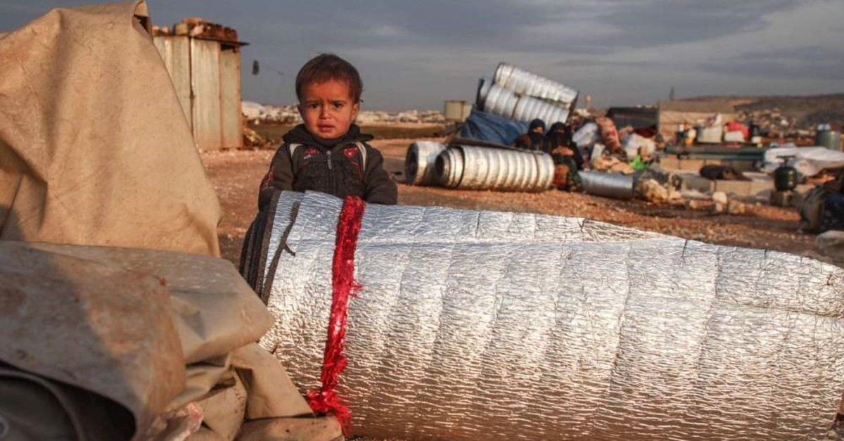 A child stands behind rolled-up thermal insulation foil out in the open at a camp for displaced Syrians east of Sarmada in the north of the northwestern Idlib province as people prepare to flee the camp, Feb.16, 2020. (AFP)