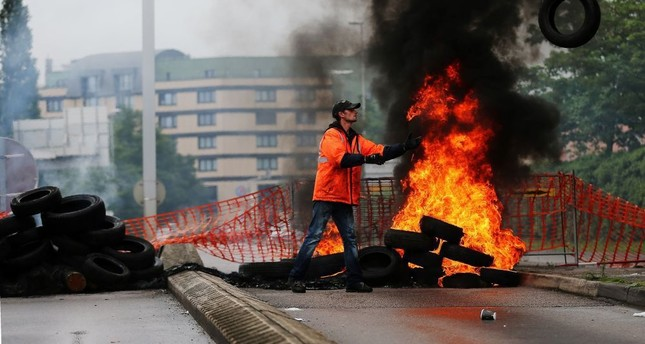 A union member throws a tire onto a pile set ablaze at a blockade onto a main road leading to downtown Rouen, northwestern France, May 31.