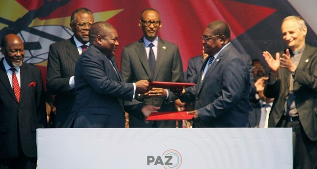 Mozambican President Filipe Nyusi, left, and Renamo leader Ossufo Momade exchange documents, at a signing agreement in Maputo, Mozambique, Tuesday, Aug. 6, 2019. AP Photo