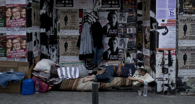 Two homeless men sleep outside the entrance of a boarded up store in central Athens .